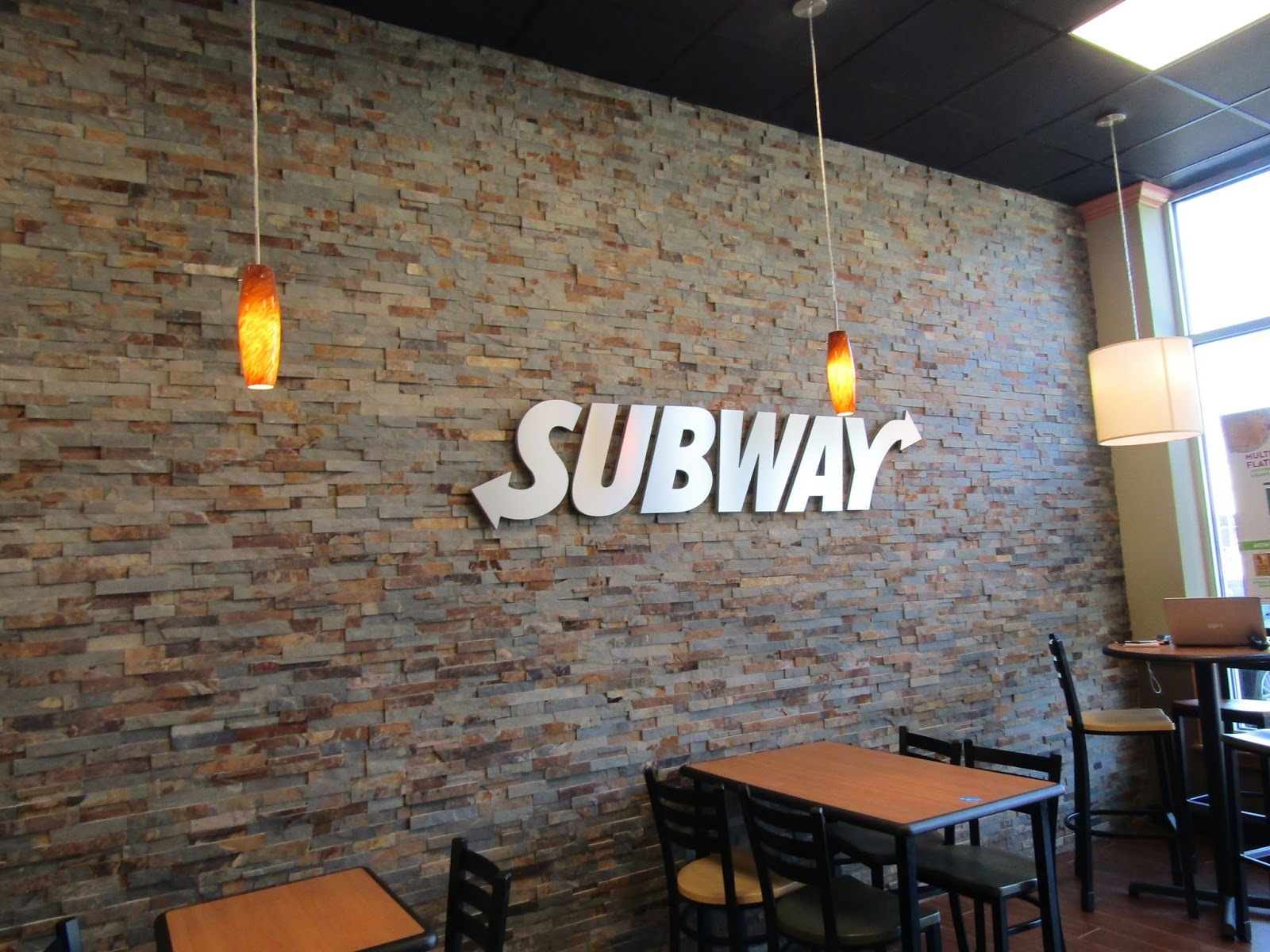 the focal point of subways metro decor is the stone wall displaying a metal version of the iconic subway logo the high ceilings give it a more spacious - Metro Decor