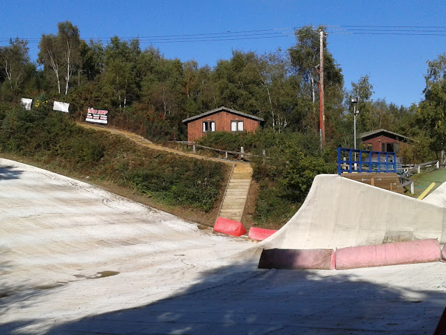 Dry ski slope overlooked by a lodge on a hill