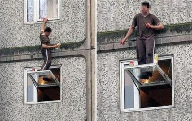 Silly man bloke does silly thing standing on glass window