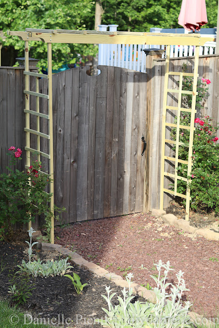 Garden arbor by a tall privacy fence, surrounding a garden path.