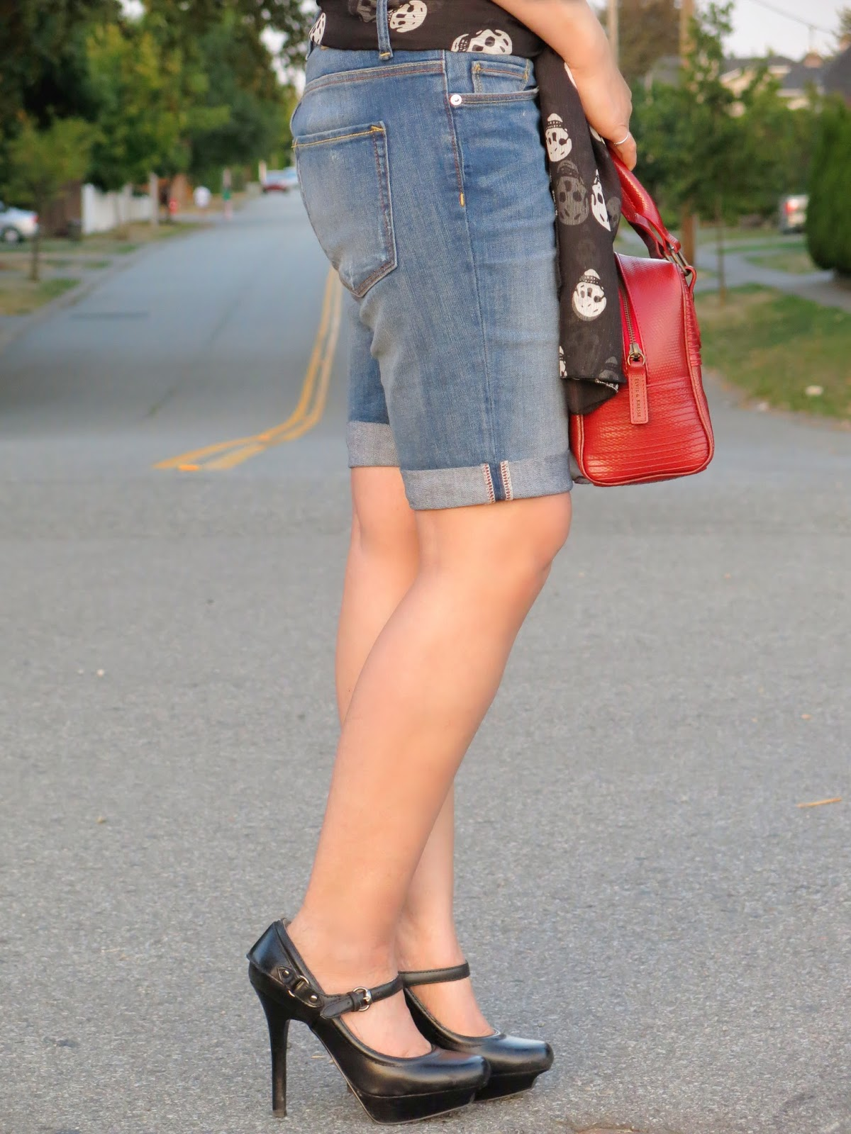 styling denim bermuda shorts with platform mary-jane shoes, a scull-print scarf, and Elvis & Kresse bag