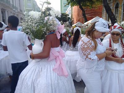 Fotografia colorida. Várias mulheres vestidas de branco, vestidos longos de saia rodada ou blusas e calças compridas, usando turbantes brancos, com detalhes em rosa  e em vermelho. Uma delas segura um vaso branco com flores do campo brancas.