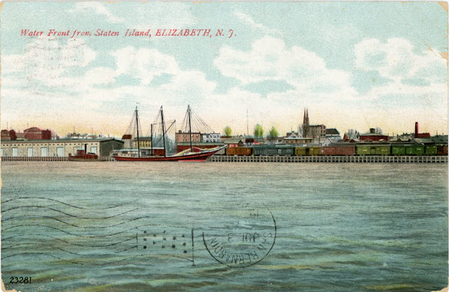 Viewed from Staten Island, this post card view of the waterfront of the city of Elizabeth, New Jersey shows a sailing ship, rail cars, and the distincitve spires of St. Patrick's Church. Postmarked 1909, sent by Louise Scheerer to Mina Krieger.