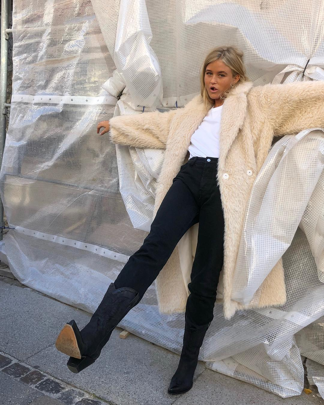How a Swedish It Girl Wears Cowboy Boots — Josefine H.J in a beige faux fur coat, white t-shirt, black jeans and western boots