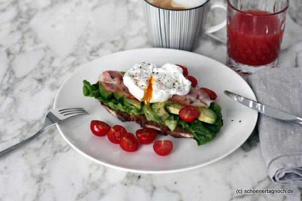 Pochiertes Ei auf geröstetem Brot mit Salat, Avocado, Bacon und Kirschtomaten