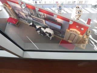 a view down from the Sioux City Skywalks at the entrance to the Sioux City Public Museum, including a large cow statue and bright red painted display walls