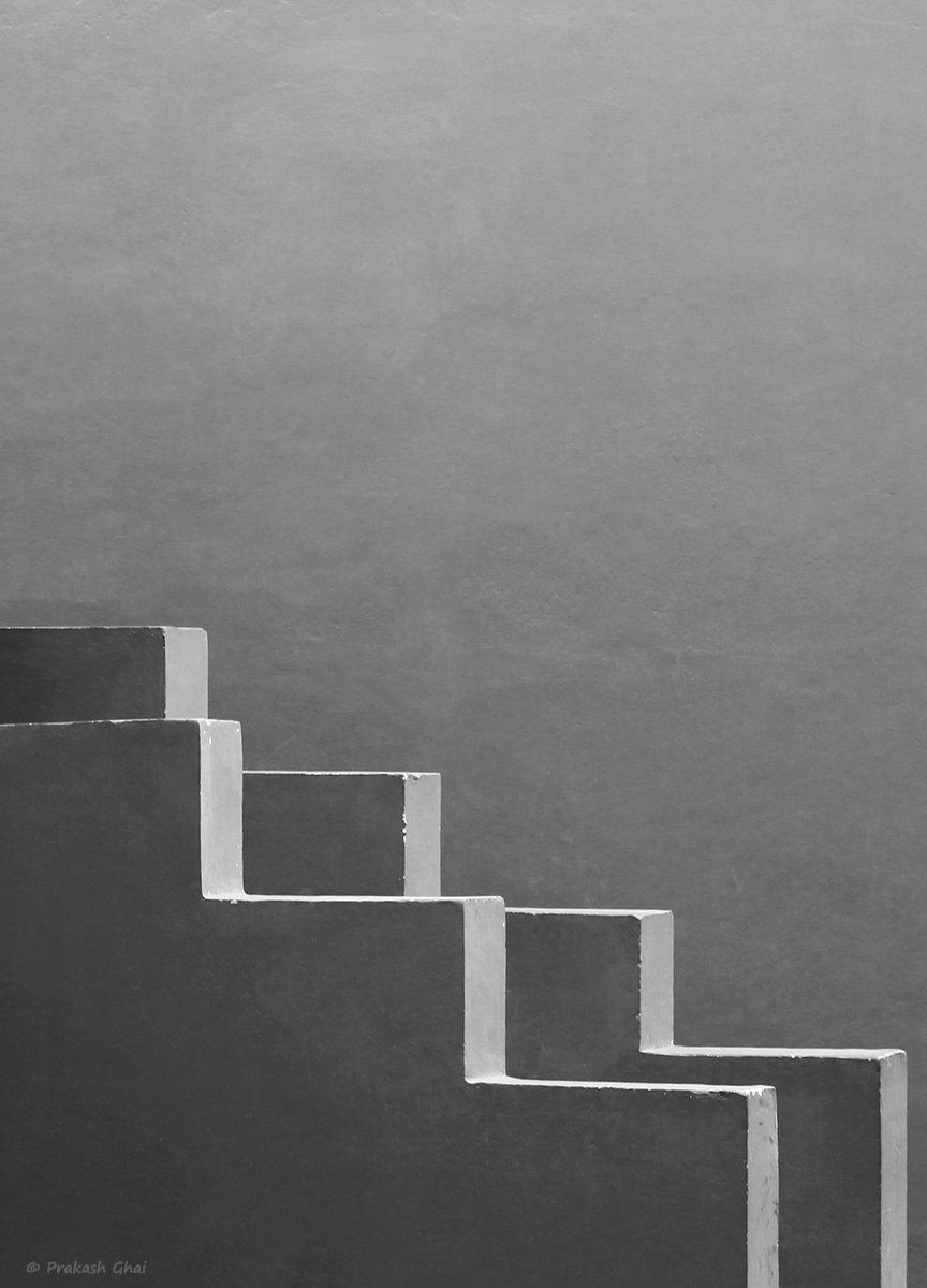 A black and white minimalist photo of the side rail zig zag pattern of a staircase