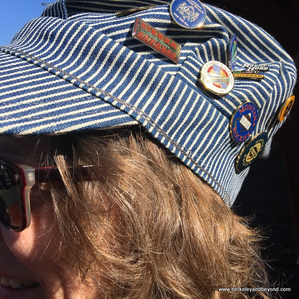 Ginger Dingus wears her engineer's hat with pins from prior train trips,  at Railtown 1897 State Historic Park in Jamestown, California