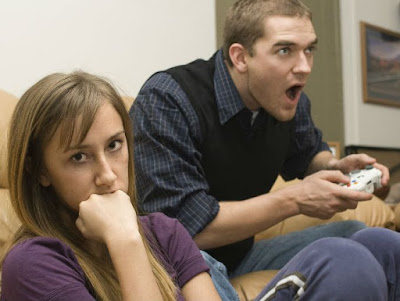 una mujer aburrida ignorando a su marido que juega video juegos