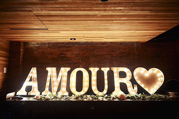 Marquee light rentals from Bespoke Decor spell out AMOUR with a heart at the end