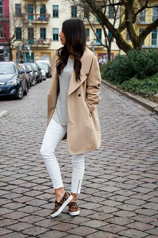 She is wearing a camel coat, white stripe top, white pants and animal print slip on sneakers
