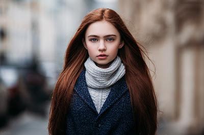 Chica pelirroja abrigada mirando a cámara con fondo difuminado