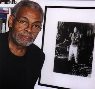 Amiri Baraka con la foto di Paul Robeson alle spalle