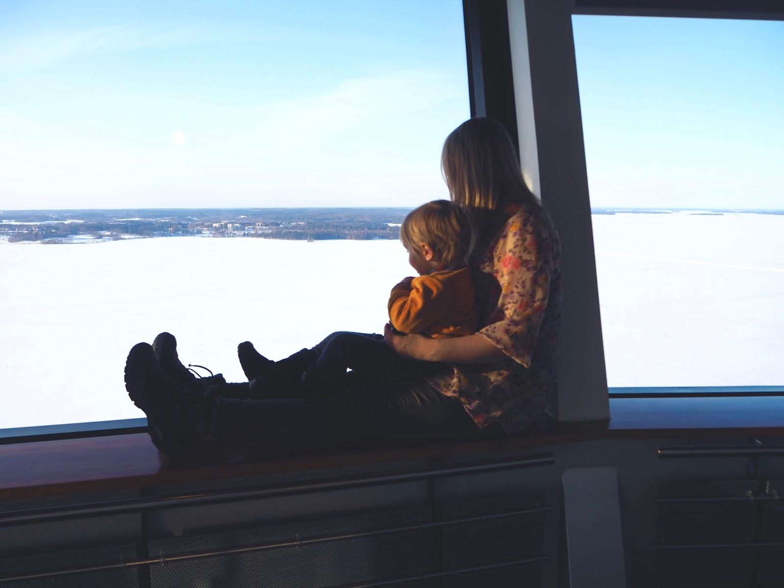 Äiti ihailee maisemaan poika sylissään Tampereen Näsinneulassa.