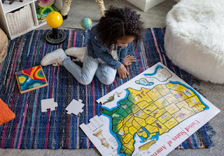 A little girl looks at a map of the United States