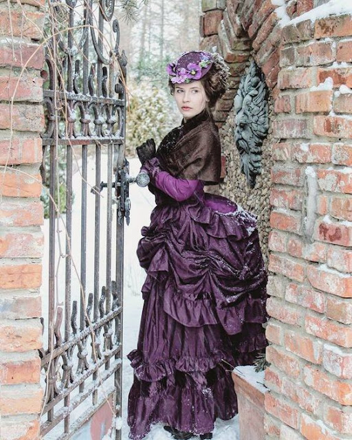 Woman in Victorian clothing (purple bustle skirt, bodice, shawl, hat with flowers, gloves) walking through a gate in the winter snow