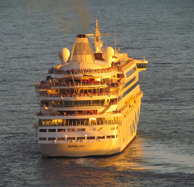 AIDAvita cruise ship leaves Funchal port with a beautiful sunlight