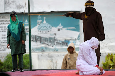 A Muslim woman is caned in Banda Aceh, Indonesia, for breaking sharia law.