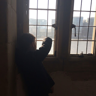 Boy looking out of window at city