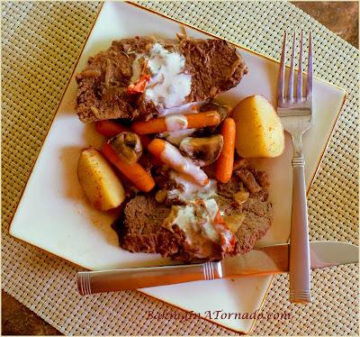 Slow Cooker Red Wine Sour Cream Roast: A sirloin roast, mushrooms, baby carrots and potatoes slow cooked in a red wine and sour cream sauce. | Recipe developed by www.BakingInATornado.com | #crockpot #dinner #beef