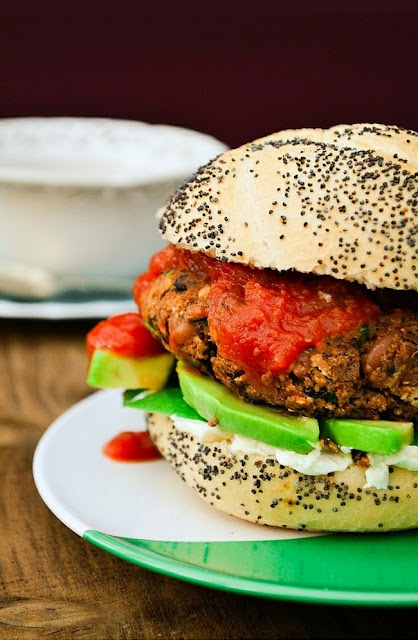 Spicy Bean Burgers stack in a bun with cream cheese, avocado and burger relish