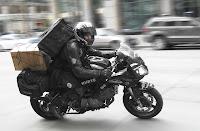 Siyah bir yarış motosikletiyle kargo kutularını dağıtan siyah giysili ve kasklı kurye