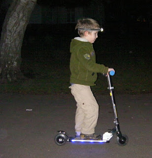 LED lit scooter in the park with head torch in the darkness