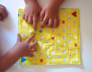Kids hands play with yellow fabric maze