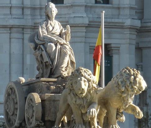Imagen de La Cibeles en primer plano, detrás una bandera de España y la fachada del Ayuntamiento de Madrid.