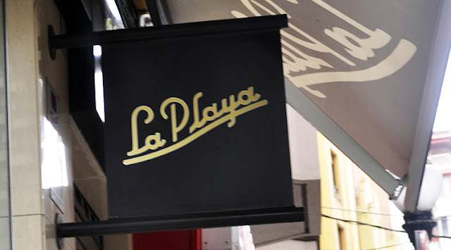 cartel en fondo negro con letras en dorado que dice La playa en letra cursiva