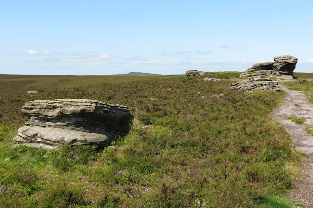 A view across moorland, past the Ox Stones, to the start of Stanage Edge on the horizon.
