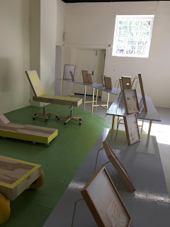 installation shot from a room with a semi-circular table or stand for photographs and sun decks made of wood, painted yellow