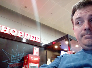 Selfie of me with Budwieser fridge under Home of the Whopper sign in the background.