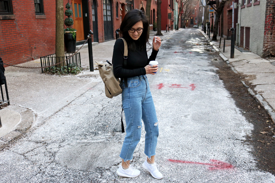 Black top, Mom Jeans, White Sneakers, Khaki Backpack