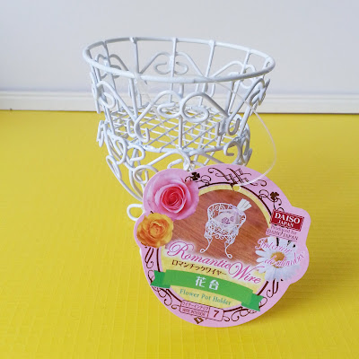 White wire flower pot holder with tag.