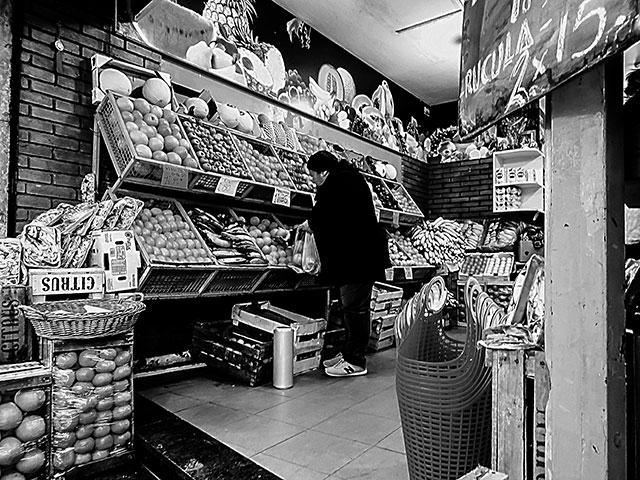 En una verdulería una mujer comprando.BYN