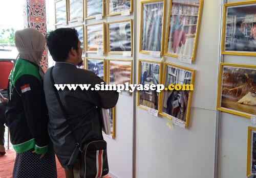 PAMERAN FOTO : Pengunjung asyik menikmati foto foto yang dipamerkan dalam Kalbar Book Fair 2016 ini.  Foto Asep Haryono