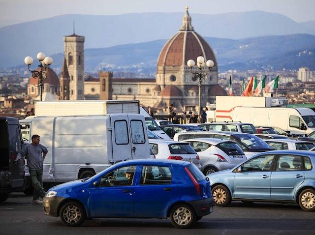 Carros estacionados e cidade de Florença ao fundo