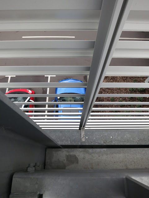 A red car and a Blue car in parking bay outside multistory car park.