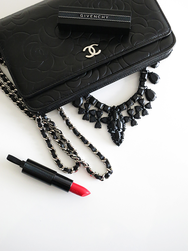 Flatlay featuring Chanel black lambskin camellia embossed wallet on chain WOC, black matte J. Crew statement necklace, Givenchy Rouge Interdit red lipstick
