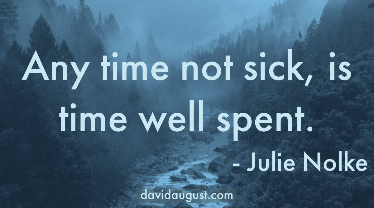 picture of a river through a wooded mountain area tinted blue with the words 'Any time not sick, is time well spent. -Julie Nolke' written on it