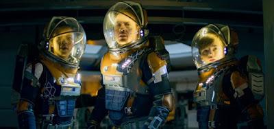 Taylor Russell (Judy), Toby Stephens (John) e Maxwell Jenkins (Will) com os trajes espaciais
