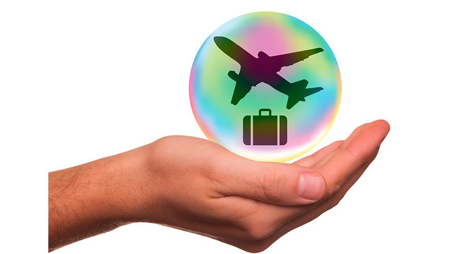 Mão segurando desenho de bolha de sabão com mala de viagem e avião