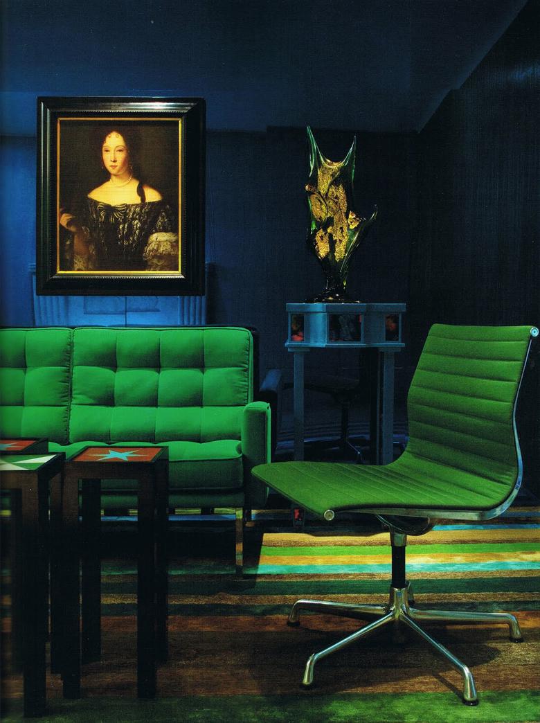 zielona sofa i granatowa ściana we wnętrzu