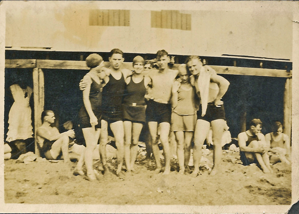 Three young men and three young women posing arm in arm on a beach. All wearing bathing suits. c. 1920's? Photo from album owned by E. Karvoius, privatley held by E. Ackermann, 2016.