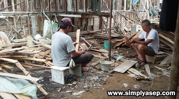 PAKU : Pak Herman, Ketua RT Blok C (kiri) dan Pak Sabiqis (Kanan) sedang mencopot paku yang masih menempel di papan papan kayu. Semangads luar biasa.  Foto Asep Haryono
