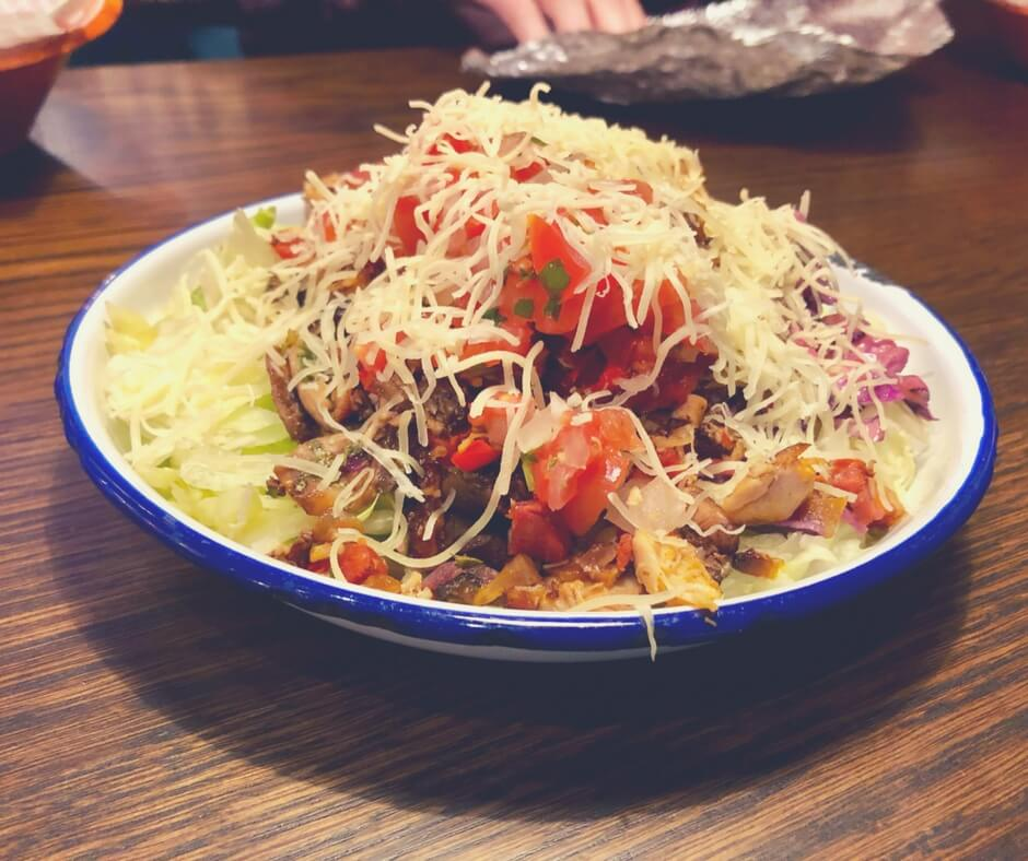 A salad bowl with lettuce, crunchy slaw, mushrooms, a chicken and chorizo mix, mild salsa, and cheese, all from Barburrito, Nottingham.