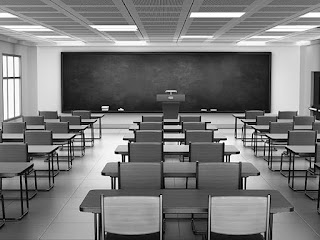 Rows of chairs and desks in a classroom facing a blackboard