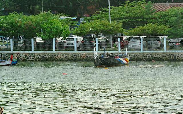 Perahu kecil dan mobil terparkir rapi di pelabuhan