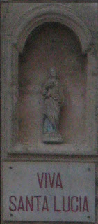 A zoomed view of the small statue and plaque that reads Viva Santa Lucia.